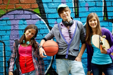 summer clothes: Row of happy teens by painted wall looking at camera Stock Photo
