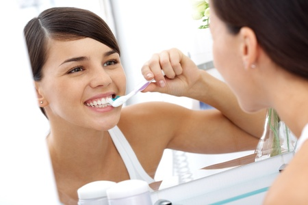 front teeth: Image of pretty female brushing her teeth in front of mirror in the morning