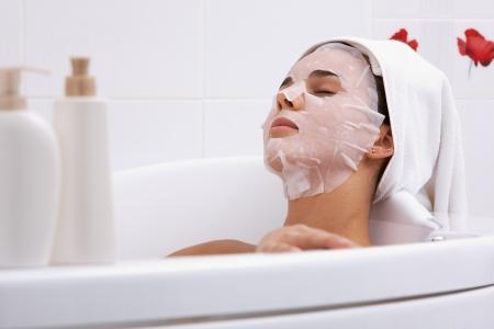Image of serene woman with facial mask enjoying bath in spa salon photo