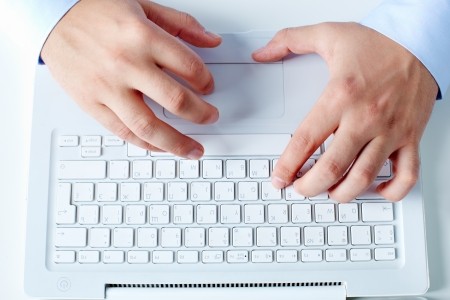 Close-up of businessman hands working with laptop at workplace photo