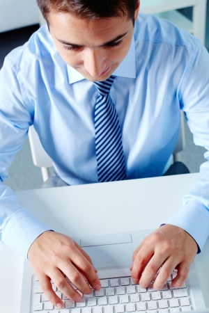 Above view of businessman working with laptop at workplace photo