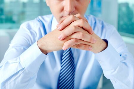 keeping: Close-up of businessman keeping fingers crossed by his face