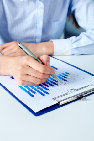 Close-up of businesswoman working with financial document photo