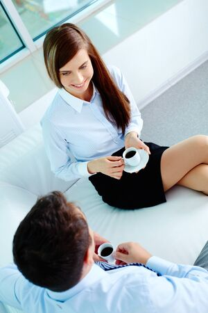 Photo of friendly business partners talking while drinking coffee in office photo