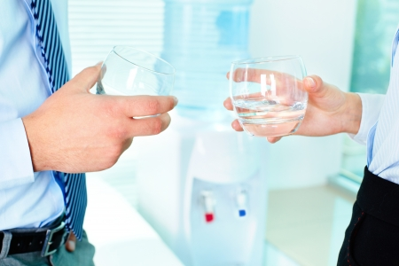 man drinking water: Photo of business partners hands holding glasses with water Stock Photo