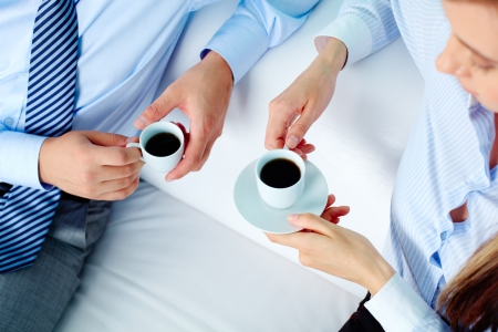 office break: Close-up of two business partners holding cups of coffee
