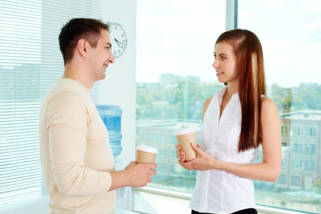 two people talking: Photo of two friendly business partners in casual clothes talking in office