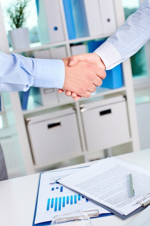Photo of handshake of business partners after striking deal on background of documents photo