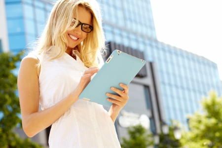 woman tablet: Portrait of pretty student or businesswoman in smart casual using digital tablet outdoors