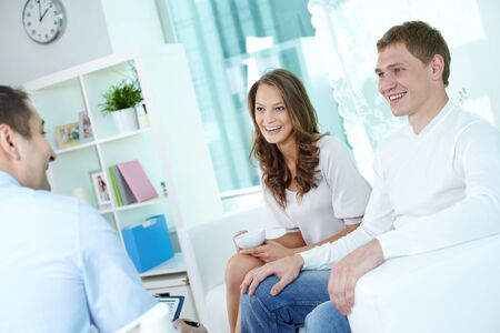 advising: Positive young couple at home having a conversation with a smiling business consultant