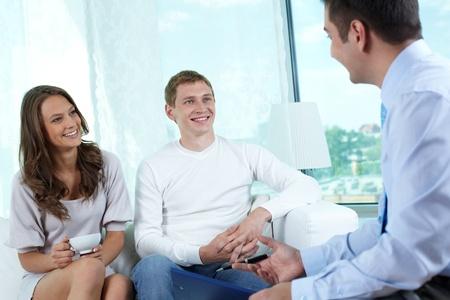 amigas conversando: Seguro de consultor o asesor financiero que tenga una charla amistosa con una joven pareja Foto de archivo
