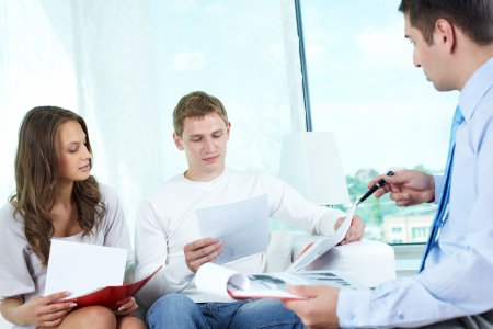 insurance consultant: Young people looking through documents to find the best insurance program