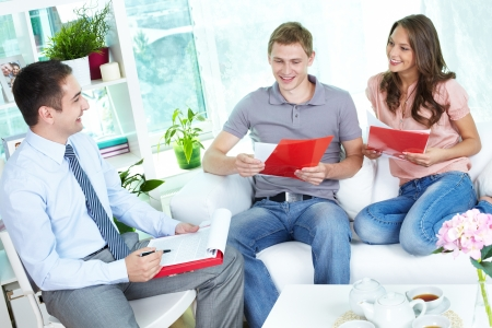signing: Financial agent holding a meeting with a young family at home discussing the terms of the contract