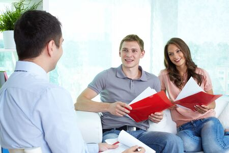 settling: Confident insurance agent settling the matters with a young cheerful couple