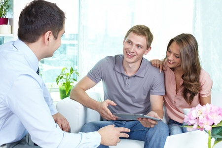 advising: Businessman showing a business plan or insurance program on the screen of the pad to the young people