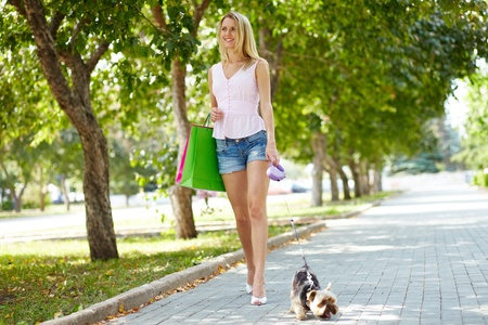 Portrait of happy female strolling with adorable pet in park