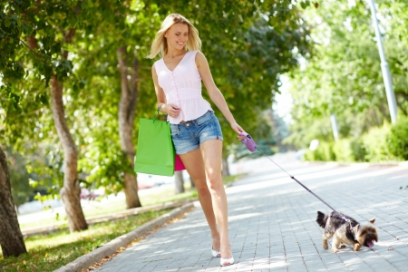 strolling: Portrait of happy female strolling with her pet at leisure