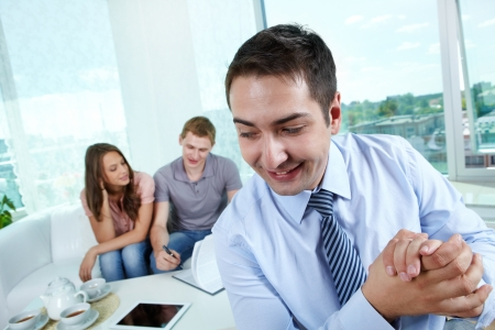 dishonest: Cunning manager rubbing his hands while his unaware clients signing the contract Stock Photo