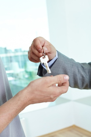 doorkey: Real estate agent passing the key to the house to a satisfied male homeowner