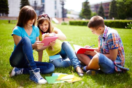 Cute high-school students doing homework outdoor on the lawn