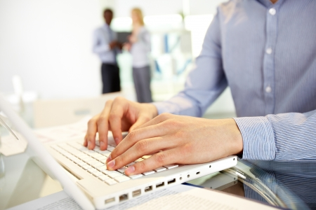 computer programmer: Image of human hands typing in the foreground, business colleagues can be recognized in the blurred background Stock Photo