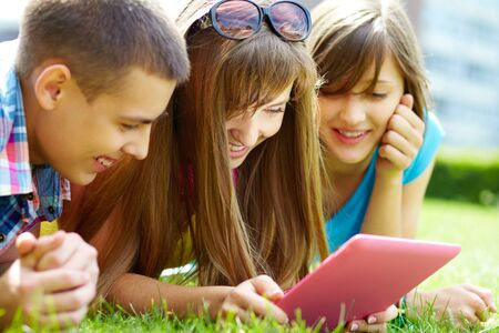 interested: Laughing teenagers looking at the touchpad screen outdoors