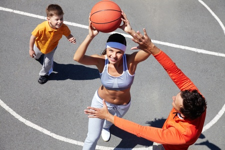 dynamic activity: Cheerful family of three playing amateur basketball
