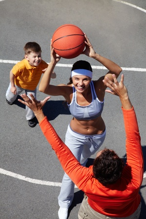 dynamic activity: Young woman throwing the ball, her husband trying to block Stock Photo