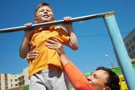 apoyo familiar: Kid haciendo barbilla-sube, su padre le ayuda a