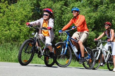 andando en bicicleta: La imagen dinámica de un ciclo de familia en el parque Foto de archivo