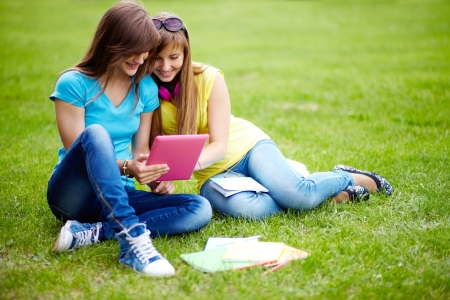 gadget: Cute girls sitting on the lawn and using the tablet computer