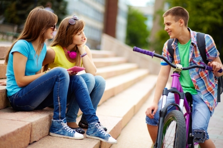 interested: Teen girls seeming to be interested in the guy riding the bike