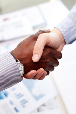 evoking: Vertical shot of a firm business handshake guaranteeing safety and evoking trust