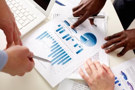Gli uomini d'affari che parlano le tabelle e grafici che mostrano i risultati del loro successo il lavoro di squadra