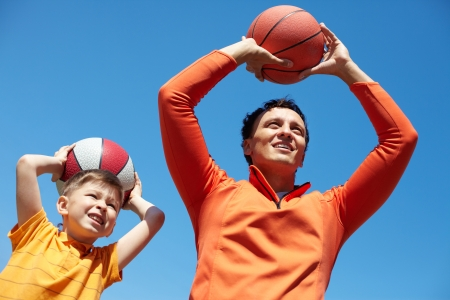 Father and son spending time together playing basketball photo