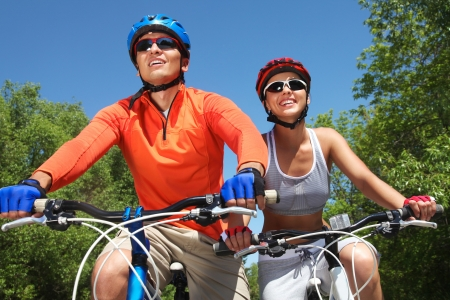 cycling   helmet: Young smiling couple cycling through summer park