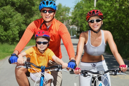 Active family of three riding their bikes in summer photo