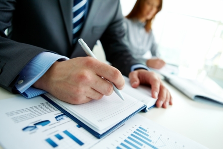 business management: Unrecognizable business person analyzing graphs and taking notes Stock Photo