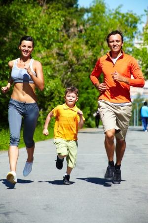enduring: Vertical shot of three cheerful runners