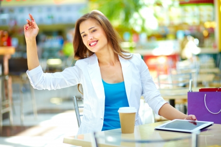well dressed girl: Elegant woman sitting at table asking for the bill by gesture Stock Photo