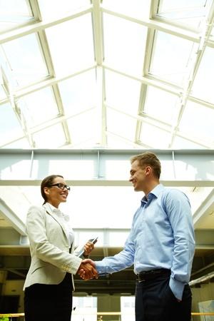 personas saludandose: La gente de negocios d�ndose la mano con una sonrisa la celebraci�n de un acuerdo o salud�ndose