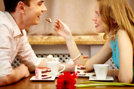 indulging: Young people sitting in the cafe and eating dessert, girl shares the cake with her boyfriend