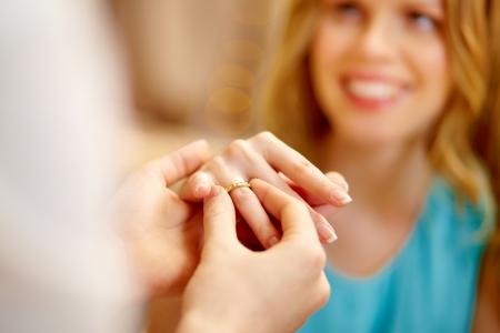 verlobung: Guy Putting einen Verlobungsring am Finger von seiner Freundin Lizenzfreie Bilder