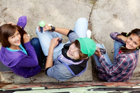 Group of teenagers with aerosol paint sitting and looking up at the camera photo