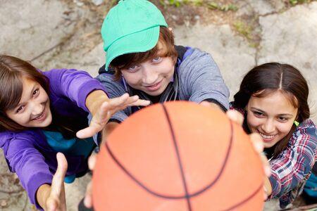 baloncesto chica: Adolescentes alegres que juegan a baloncesto en la calle con el balón cerca de la cámara