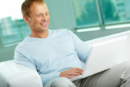 portables: Smiling man using his laptop to surf the internet  Stock Photo