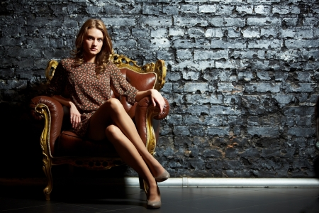 high fashion: Gorgeous girl sitting in a vintage chair presenting the contrast of high fashion and grunge
