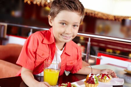 sweettooth: Portrait of a cute boy with three portions of dessert at the cafe Stock Photo