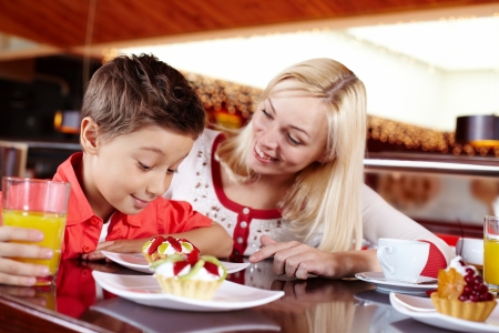 sweettooth: Mother treating her son to a delicious tart with cream and fruit Stock Photo