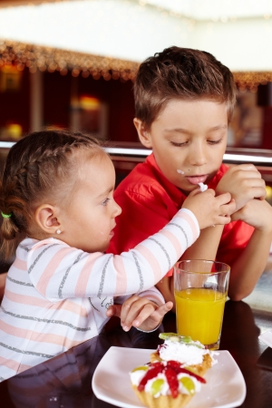 Little girl sharing her dessert with her brother photo